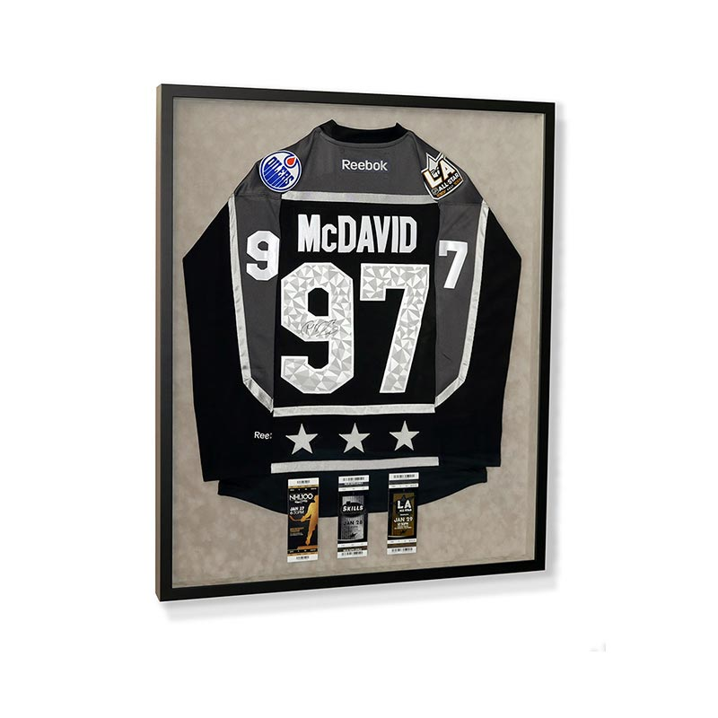 L.A. Kings number 97 McDavid jersey in a black frame on velvet grey mat with three game ticket insets